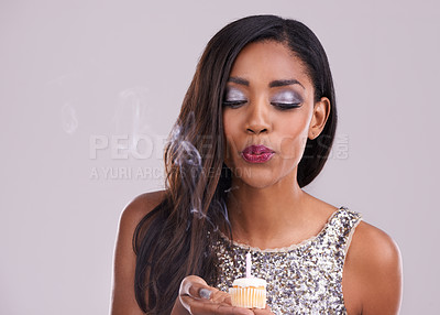 Buy stock photo Studio shot of a gorgeous  young woman blowing out the candle on a cupcake against a gray background