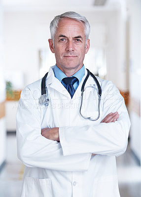 Buy stock photo Portrait of a confident mature doctor standing in a hospital hallway