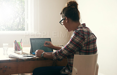 Buy stock photo Rearview shot of a young student working on her digital tablet at home