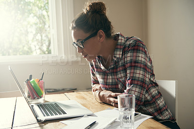 Buy stock photo Cropped shot of an attractive young student working on her laptop at home