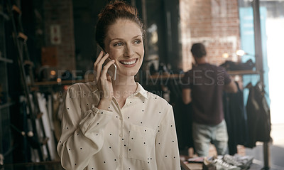 Buy stock photo Shot of a young shop owner talking on the phone with a customer in the background