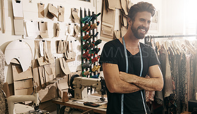 Buy stock photo Shot of a handsome young tailor standing in his workshop