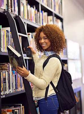 Buy stock photo Portrait of a female student standing with a book beside a bookshelf in a library