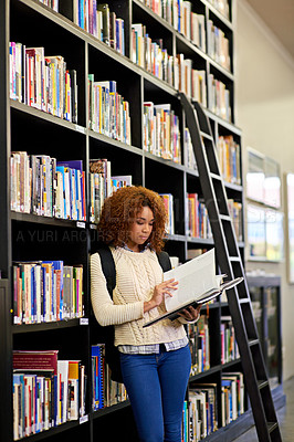 Buy stock photo Shot of a young woman studying from a book while standing by a library bookshelf