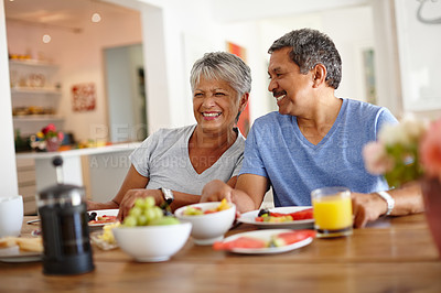 Buy stock photo Shot of a happy senior couple enjoying a leisurely breakfast together at home