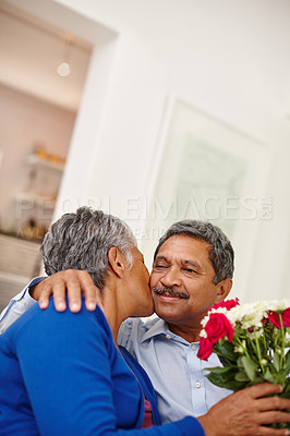Buy stock photo Shot of a loving senior man giving his wife a bunch of flowers