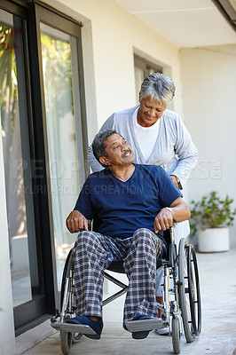 Buy stock photo Shot of a senior woman pushing her husband in a wheelchair outdoors