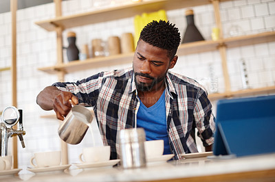 Buy stock photo Cropped shot of a handsome male barista preparing coffee behind a cafe counter