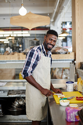 Buy stock photo Cropped portrait of a handsome young man preparing food in the kitchen of his cafe