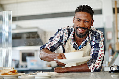 Buy stock photo Cropped portrait of a handsome young man serving you breakfast at a cafe
