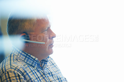 Buy stock photo Shot of a senior businessman wearing a headset looking thoughtful in the office