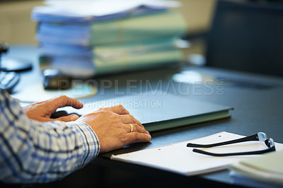 Buy stock photo A businessman's arms resting on a book on his desk with his glasses and a notebook beside him