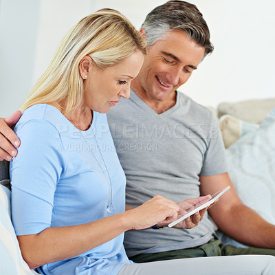 Buy stock photo Shot of a mature couple sitting at home using a digital tablet