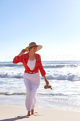 Buy stock photo Shot of an attractive mature woman enjoying a day at the beach
