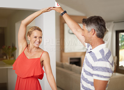 Buy stock photo Shot of a happily married couple dancing together at home