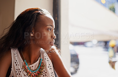 Buy stock photo Shot of an attractive young woman sitting in a cafe