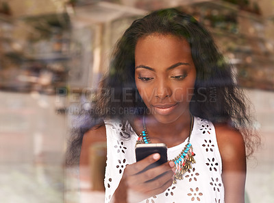 Buy stock photo Shot of an attractive young woman reading a text message on a mobile phone in a cafe