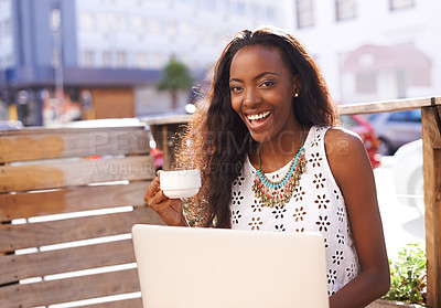 Buy stock photo Shot of a young woman using a laptop at a cafe outside