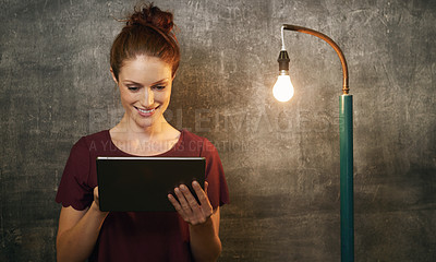 Buy stock photo Cropped shot of an attractive young woman using a tablet against a grunge background