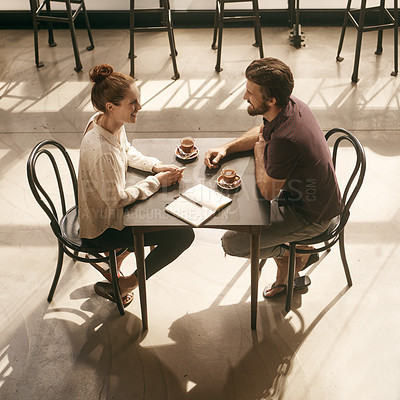 Buy stock photo High angle shot of a young couple having coffee in a cafe
