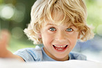 Cheerful little boy with grey eyes smiling