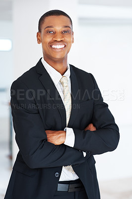 Buy stock photo Potrait of a confident young businessman standing with his hands folded  at office