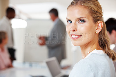 Buy stock photo Portrait of a smart young businesswoman in meeting with colleagues in background