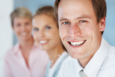 Buy stock photo Closeup of a happy young businessman with his colleagues in background