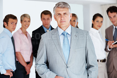 Buy stock photo Portrait of a mature businessman standing in front of his successful group at office