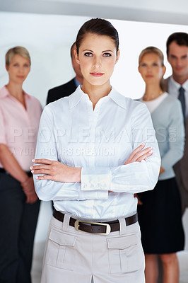 Buy stock photo Portrait of a successful young businesswoman with her team at the back
