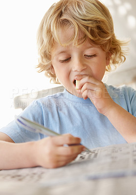 Buy stock photo Portrait of an innocent boy solving puzzle while eating something