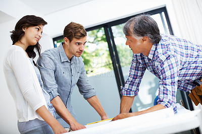Couple with architect discussing home plan on blueprint