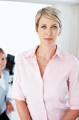 Buy stock photo Portrait of a smart young businesswoman looking conidently and her colleagues working at the back