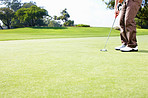 Male golfer putting the ball
