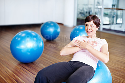 Woman doing sit ups on exercise ball