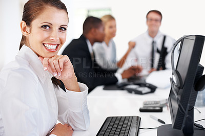 Buy stock photo Young female business executive sitting by the desk with her team working in background