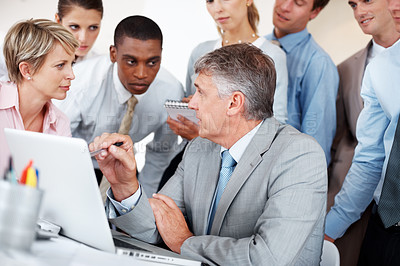 Buy stock photo Portrait of a mature businessman with his team working on laptop - Business meeting