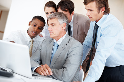 Buy stock photo Portrait of a mature businessman using laptop with his team at  office - Presentation