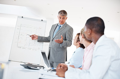 Buy stock photo Portrait of a successful senior manager giving presentation to his colleagues at office