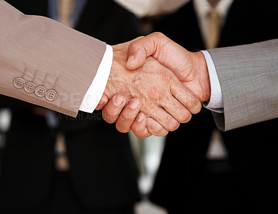 Buy stock photo Closeup of business people shaking hands to conclude a deal with colleagues in background