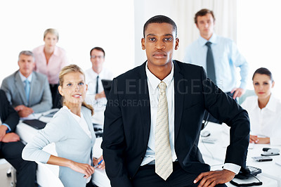 Buy stock photo Smart young african american businessman sitting on desk with his colleagues working behind in an office