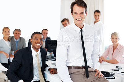 Buy stock photo Successful young businessman sitting on desk with his colleagues at the back