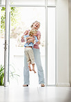 Cheerful mature woman carrying a boy at home