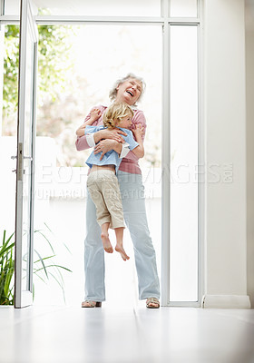 Buy stock photo Full length of a cheerful mature woman carrying a boy at home