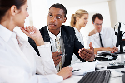 Buy stock photo An african american businessman discussing new business plan with colleague at office