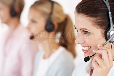 Buy stock photo Closeup of call center executive answering a call with team in background