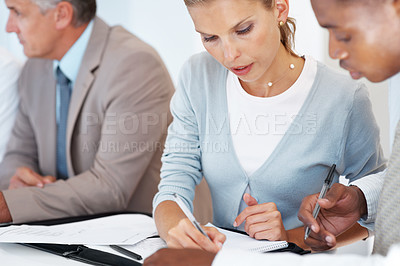 Buy stock photo Team of young professionals working on new business project at a meeting