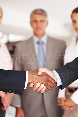 Buy stock photo Closeup of a multiracial handshake between two business men with colleagues at the back