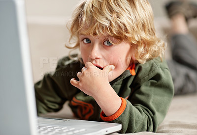 Buy stock photo Portrait of a young boy working on his laptop while lying on the floor at home