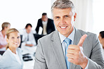 Mature businessman gesturing thumbs up sign with team working in